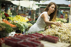 Young woman picking fresh vegetable at the market Stock Photos