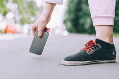 Young woman picks up from the asphalt fallen not crashed smartphone. The back cover of the phone royalty free stock photos