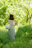 Young woman on the picnic with basket in a long skirt with a flo Royalty Free Stock Photo