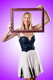 Young woman with picture frame on white Royalty Free Stock Image