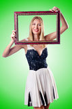 Young woman with picture frame on white Royalty Free Stock Photos