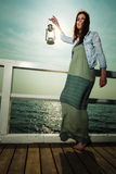 Young woman on pier with oil kerosene lamp. Stock Photography