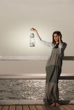 Young woman on pier with oil kerosene lamp. Royalty Free Stock Photos