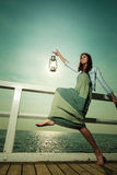 Young woman on pier with oil kerosene lamp. Royalty Free Stock Photo