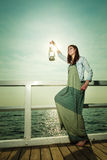 Young woman on pier with oil kerosene lamp. Stock Image