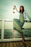 Young woman on pier with oil kerosene lamp. Royalty Free Stock Photography