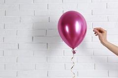 Young woman piercing bright balloon near wall, space for text. Young woman piercing bright balloon near brick wall, space for text royalty free stock photos