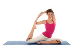 Young woman in pigeon pose. Woman Posing On A Blue Yoga Mat Stock Photos