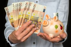 Young woman with piggy bank and euro money banknotes Royalty Free Stock Image