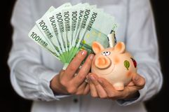 Young woman with piggy bank and euro money banknotes Stock Images