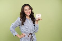 Young woman with a piggy bank on a green background.  Stock Photos