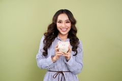 Young woman with a piggy bank on a green background.  Royalty Free Stock Image