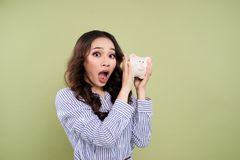 Young woman with a piggy bank on a green background.  Stock Image