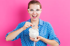 Young woman with a piggy bank. On pink background Stock Photos