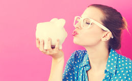 Young woman with a piggy bank. On pink background Royalty Free Stock Photo