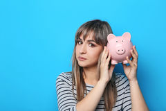 Young woman with piggy bank. Portrait of young woman with piggy bank on blue background Stock Photo