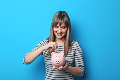 Young woman with piggy bank. Portrait of young woman with piggy bank on blue background Stock Image