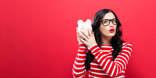 Young woman with a piggy bank. On a red background Stock Photo
