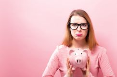 Young woman with a piggy bank. On a solid background Royalty Free Stock Image