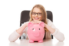 Young woman with piggybank on the desk Stock Photography