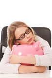 Young woman with piggybank on the desk Royalty Free Stock Image