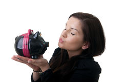 Young woman piggybank kiss. A young adult woman kissing a coinbank with closed eyes Stock Photo