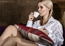 Young woman with pigtails in man`s shirt over his naked body, drinking coffee or tea sitting on a sofa.  Royalty Free Stock Photography