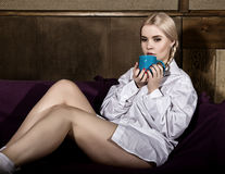 Young woman with pigtails in man`s shirt over his naked body, drinking coffee or tea sitting on a sofa Royalty Free Stock Image