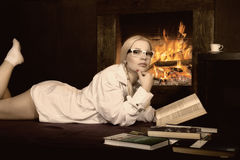 Young woman with pigtails in man`s shirt over his naked body, reading a book by fireplace stock photography