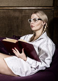 Young woman with pigtails in man`s shirt over his naked body, reading a book sitting on a sofa.  Royalty Free Stock Photos