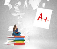Young woman on  pile of books with paper flying around Royalty Free Stock Photography