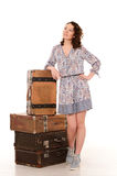 Young woman with pile of retro suitcases. Young attractive woman with wavy hair posing at pile of brown retro suitcases on white studio background Royalty Free Stock Photo