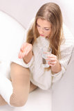 Young woman with pill and glass of water. Young long-haired blonde sitting on a sofa. She holds a pill and glass of water Royalty Free Stock Photo