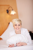 Young Woman With A Pillow On Her Bed. Young beautiful woman with a pillow on her bed Royalty Free Stock Images