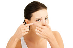 Young woman with pimple on her face. Trying to squeeze it. Royalty Free Stock Photos