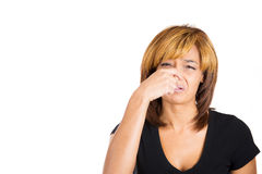 A young woman pinches her nose with disgust as something around her stinks Royalty Free Stock Images