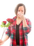Young woman pinches her nose with holding rose Royalty Free Stock Image
