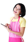 Young woman in pink apron using tablet computer Royalty Free Stock Photo