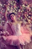 Young woman in pink ballet tutu surrounded by flowers stock photo