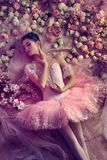 Young woman in pink ballet tutu surrounded by flowers stock image