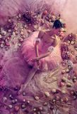 Young woman in pink ballet tutu surrounded by flowers royalty free stock images