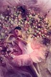 Young woman in pink ballet tutu surrounded by flowers royalty free stock photography