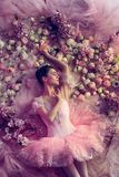 Young woman in pink ballet tutu surrounded by flowers royalty free stock photo