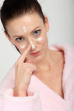 Young woman in pink bathrobe applying a cream on her nose, cheeks and forehead Stock Images