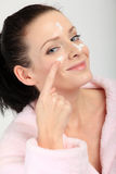 Young woman in pink bathrobe applying a cream on her nose, cheeks and forehead Royalty Free Stock Images