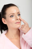 Young woman in pink bathrobe applying a cream on her nose, cheeks and forehead Royalty Free Stock Image