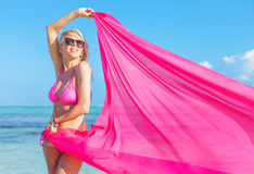 Young woman in pink bikini holding piece of fabric in wind Stock Photography