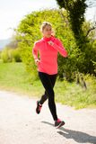 Young woman in pink and black dress runs cross country on a warm. Spring day Royalty Free Stock Photography