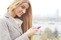 Young Woman with pink cell phone walking Royalty Free Stock Images