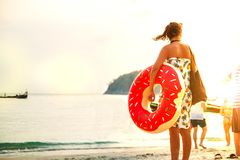 Young woman with pink circle standing on the beach. Summer vacation at sea. stock image